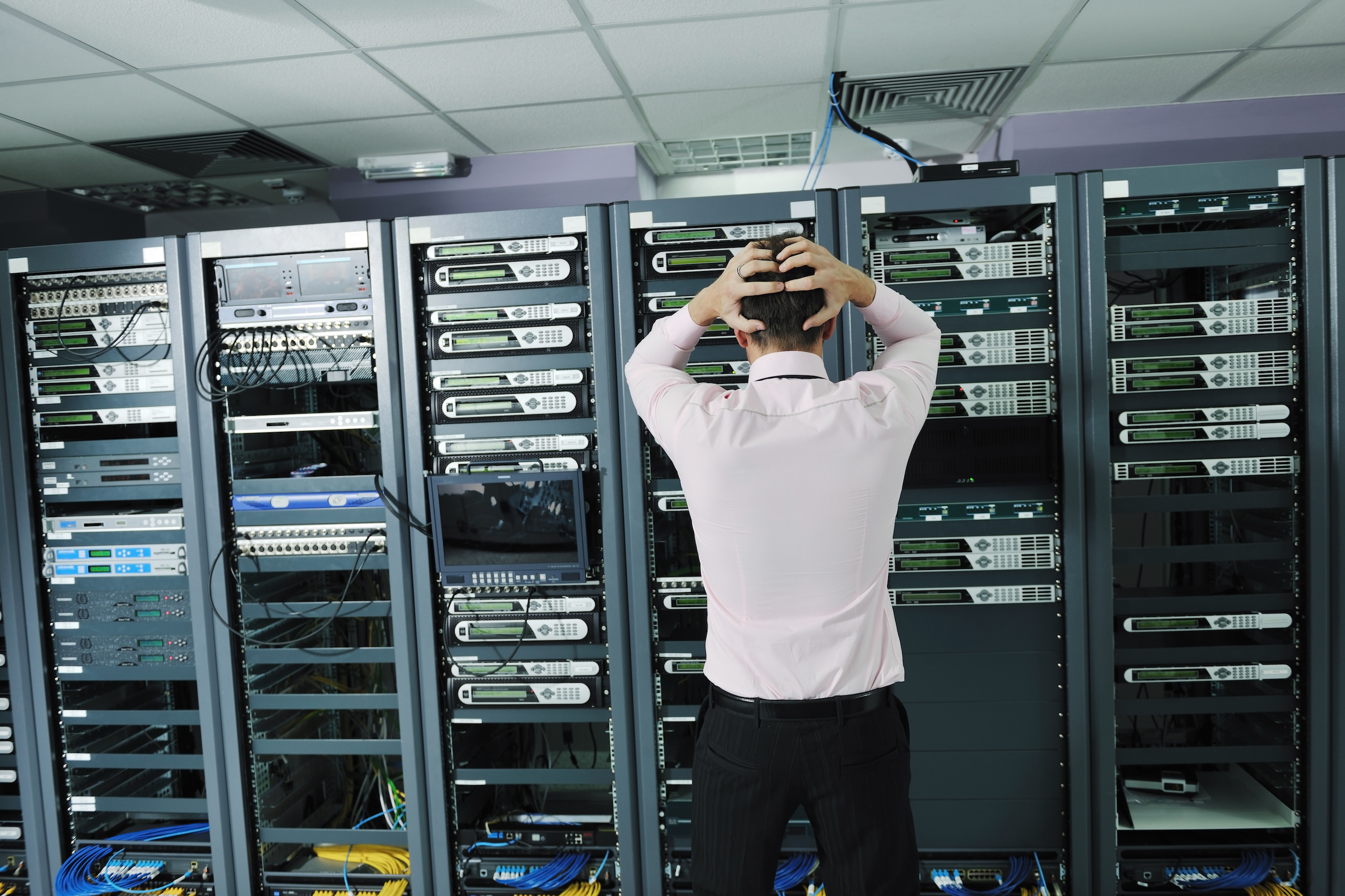 Man in data storage server room with hands in hair from frustration.